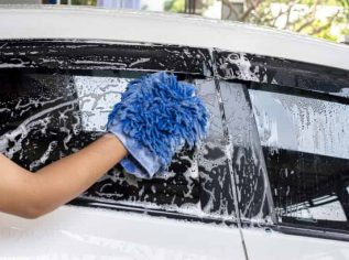 worker hand washing the exterior side windows
