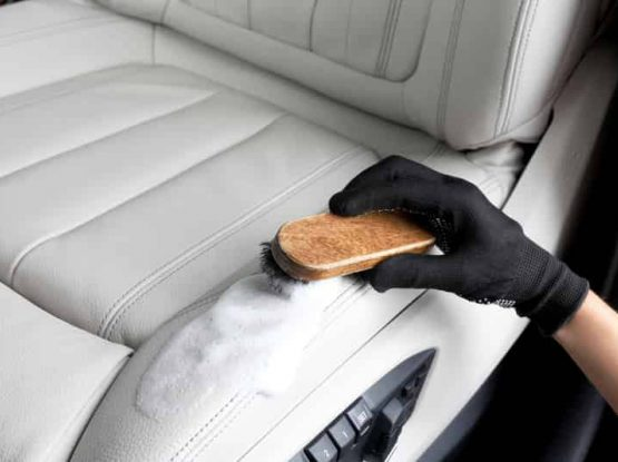 detailer cleaning seats by scrubbing the leather